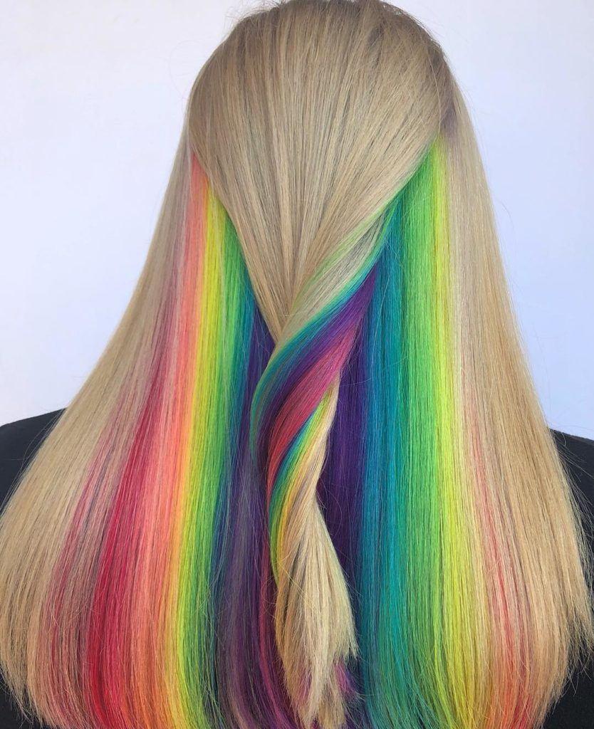Peekaboo highlights: Woman with long natural blonde straight hair with rainbow peekaboo highlights