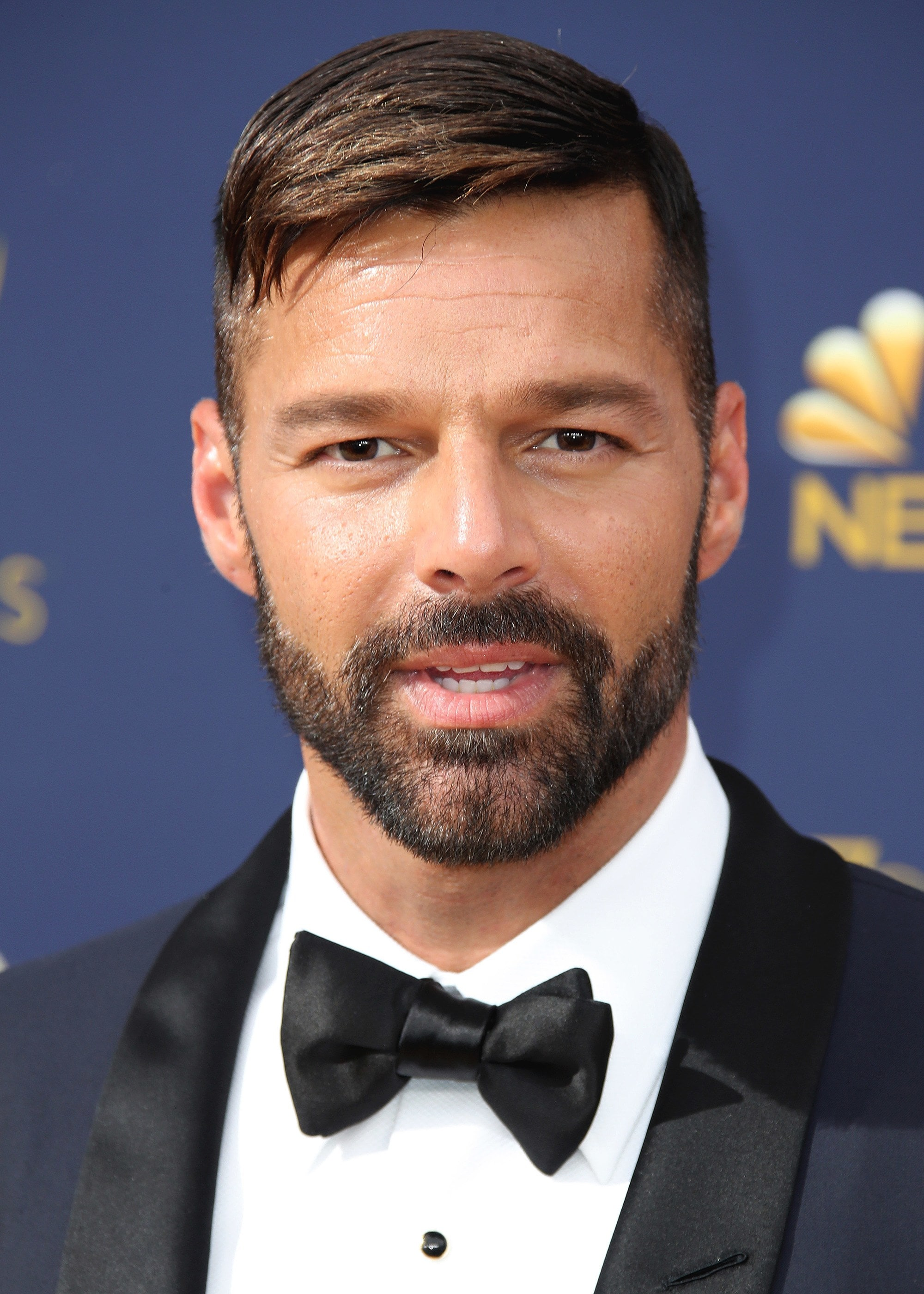 Hairstyles for receding hairline: Close-up headshot of Ricky Martin with a short combover with shorter sides and facial hair