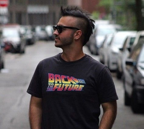 Best hair styling products for men guide: Close up shot of a man with medium, dark brown hair styled into a mohawk, wearing a top and posing in the street.