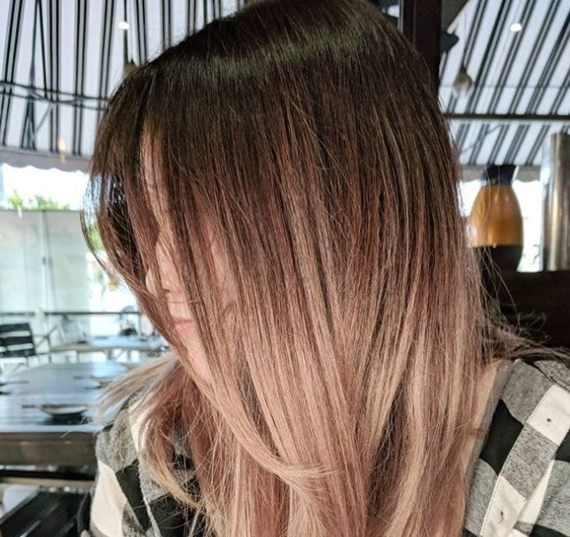 close up shot of woman with sandy pink ombre hair, wearing checked shirt and in a salon