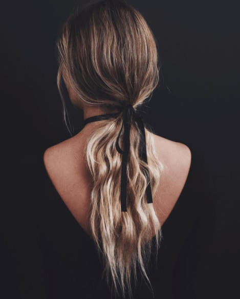 cute ponytails - model wearing loose waves with black ribbon in a messy ponytail
