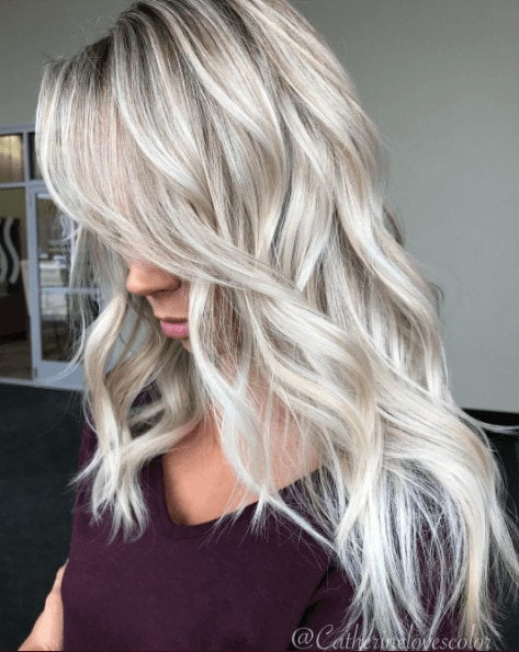 Shades of blonde hair: Woman with long wavy ice white hair wearing a black top.