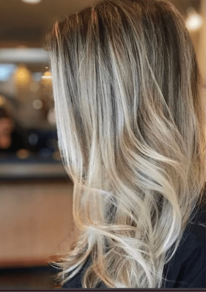 Side view of a woman's hair worn long, down and wavy blonde