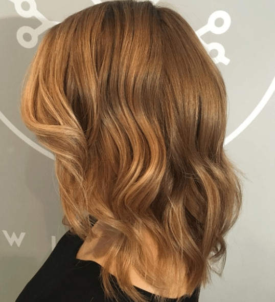 side view of a woman's hair with waves and different shades of blonde - caramel blonde hair