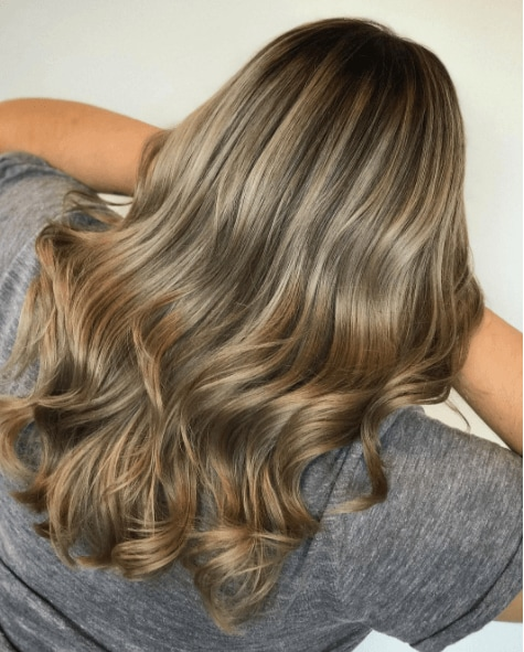 back view of a woman's hair with long waves and different shades of blonde colour