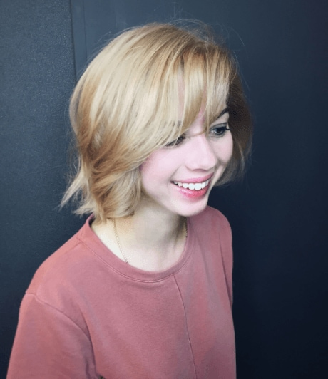 side view of a woman with short warm blonde hair