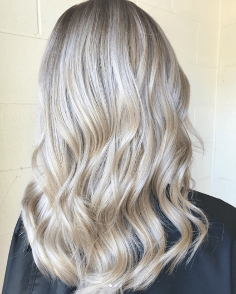 back view of a woman's long blonde hair with pearl blonde tones