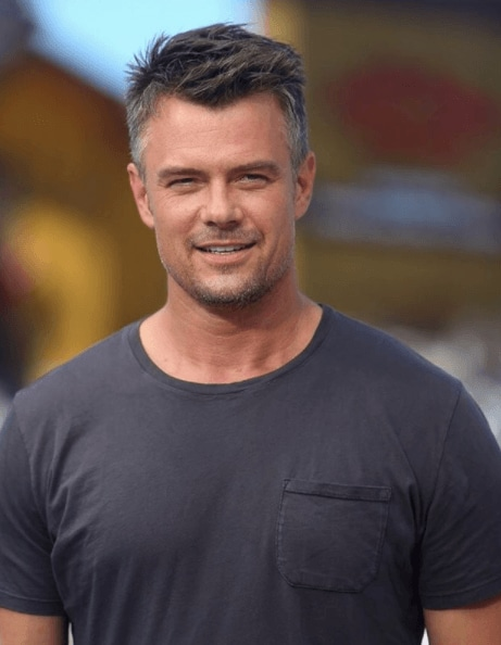 man with short hair and grey and balck colouring wearing a deep grey t shirt