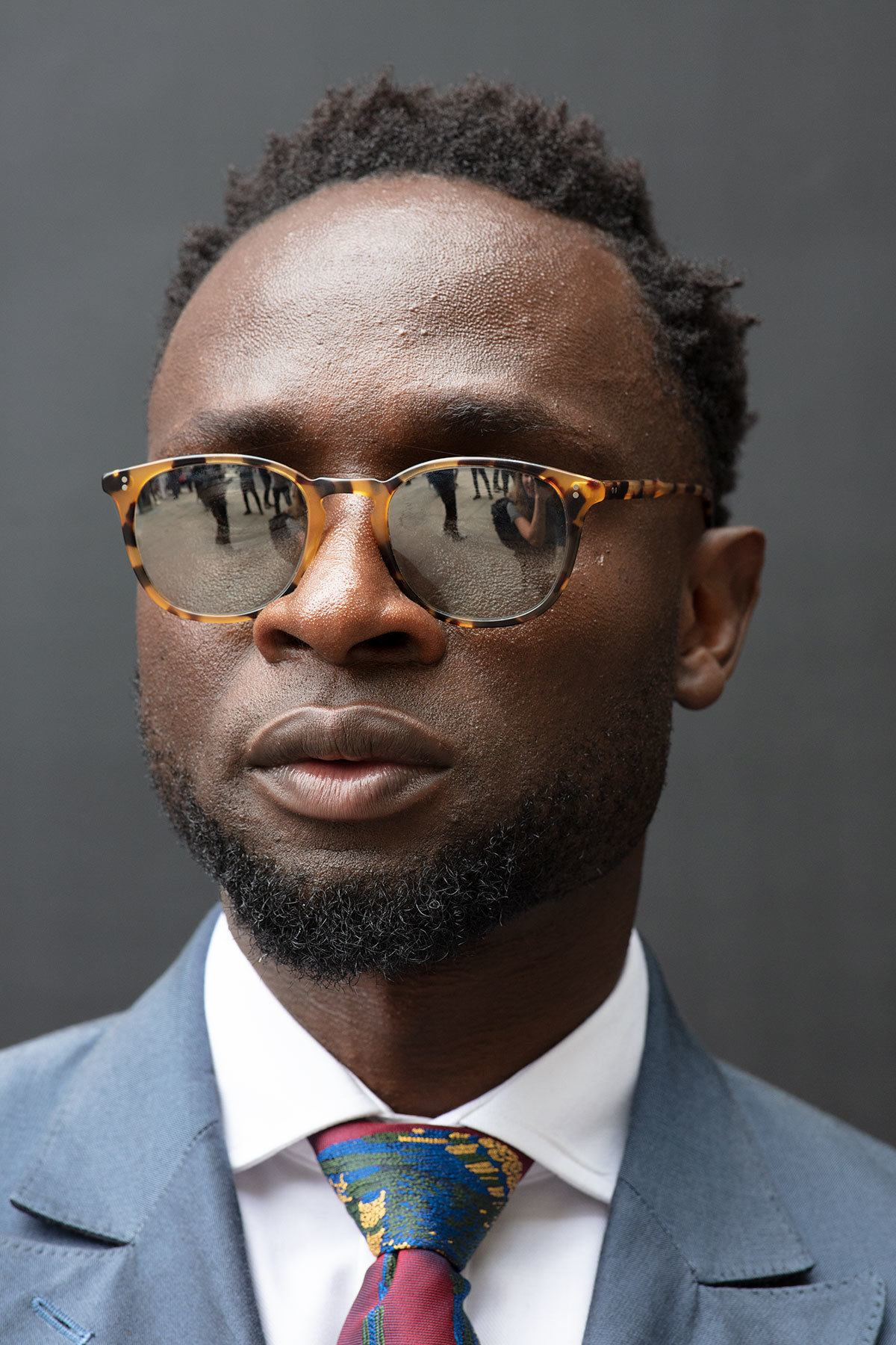 Best hair styling products for men: Close up shot of a man with short dark brown afro hair, wearing sunglasses with a suit and posing outside.