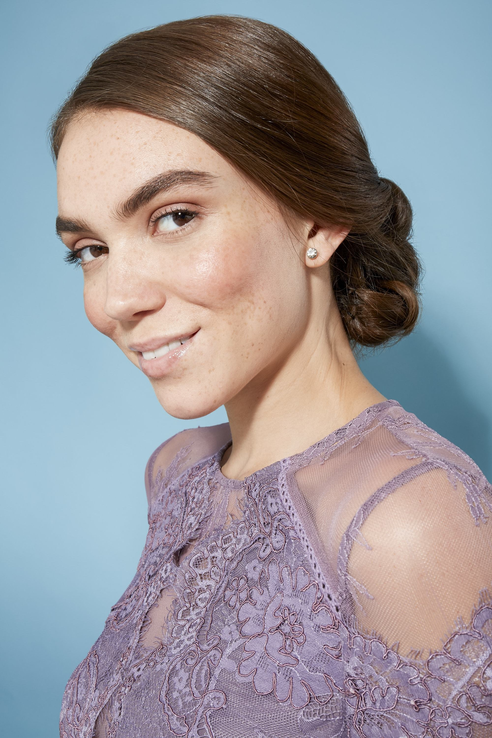 model with brown straight hair styled ina side chignon updo wearing light purple sher and lace top