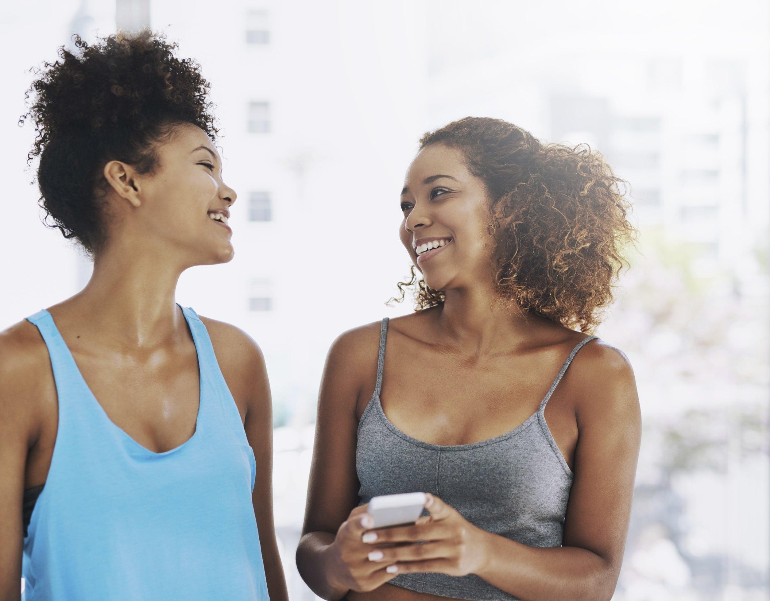 two black natural hair women laughing