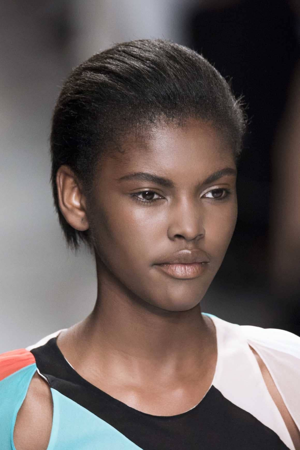 Blck woman with short slicked back hair on runway coconut oil for hair