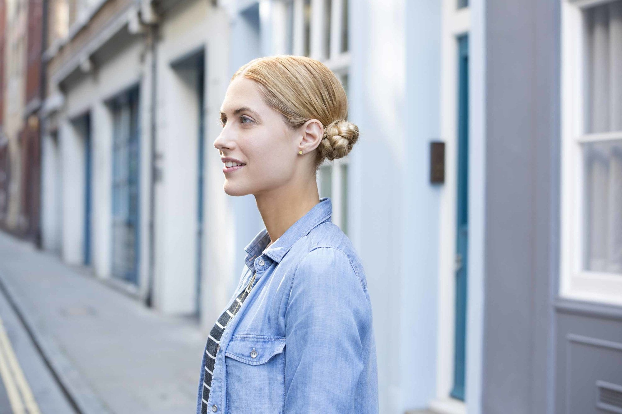 close up shot of woman outside with braided low macaron bun hairstyles, wearing denim and sporty clothing