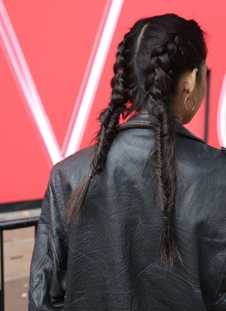 Thick hairstyles: Backshot of woman with long boxer fishtail braids, wearing a black jacket and posing outside at LFW