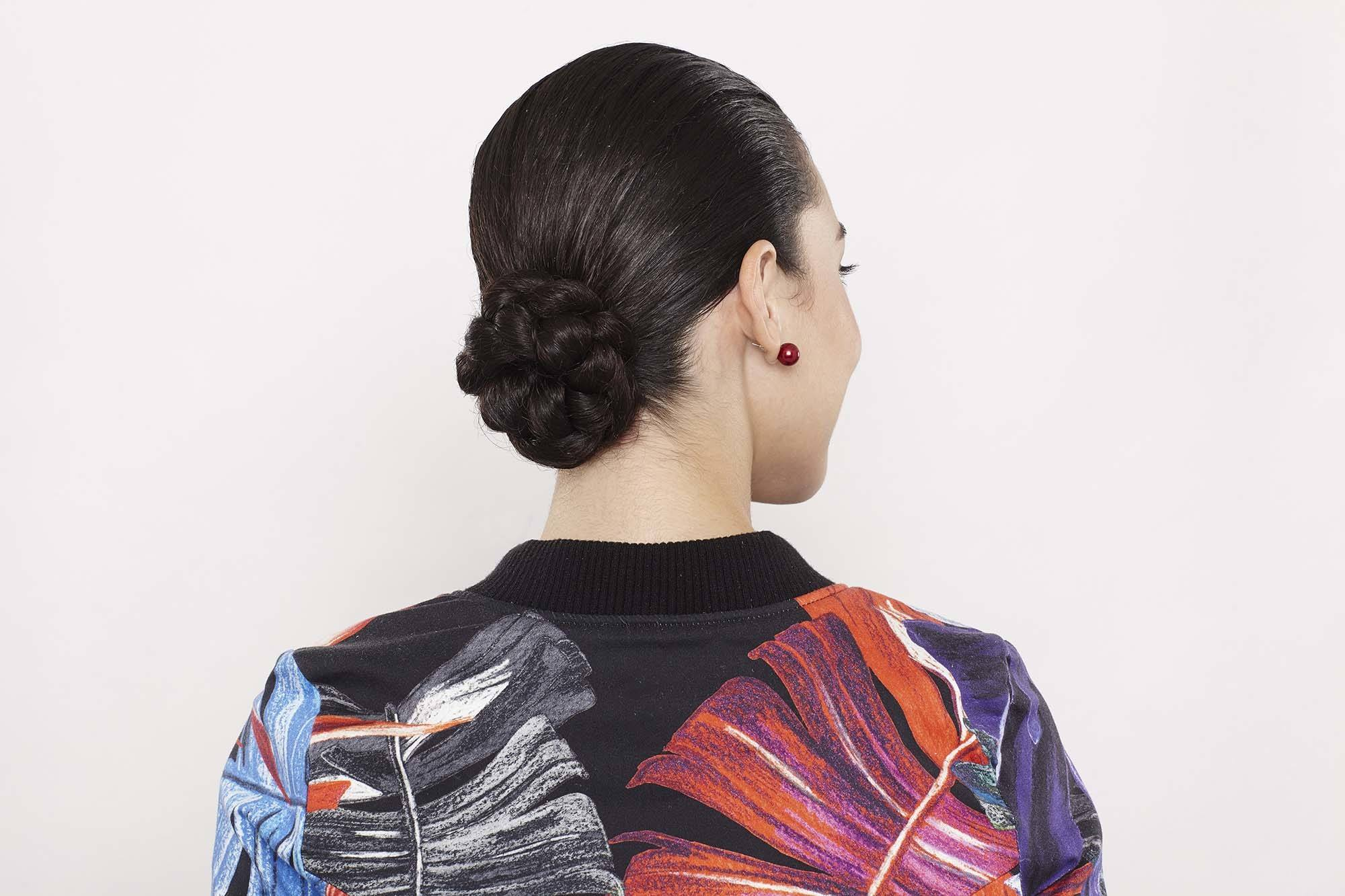 close up shot of woman with low braided bun hairstyle, wearing sporty clothing and posing in a studio