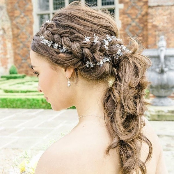Wedding hairstyles for long hair: Brunette with curly long hair in a braided ponytail