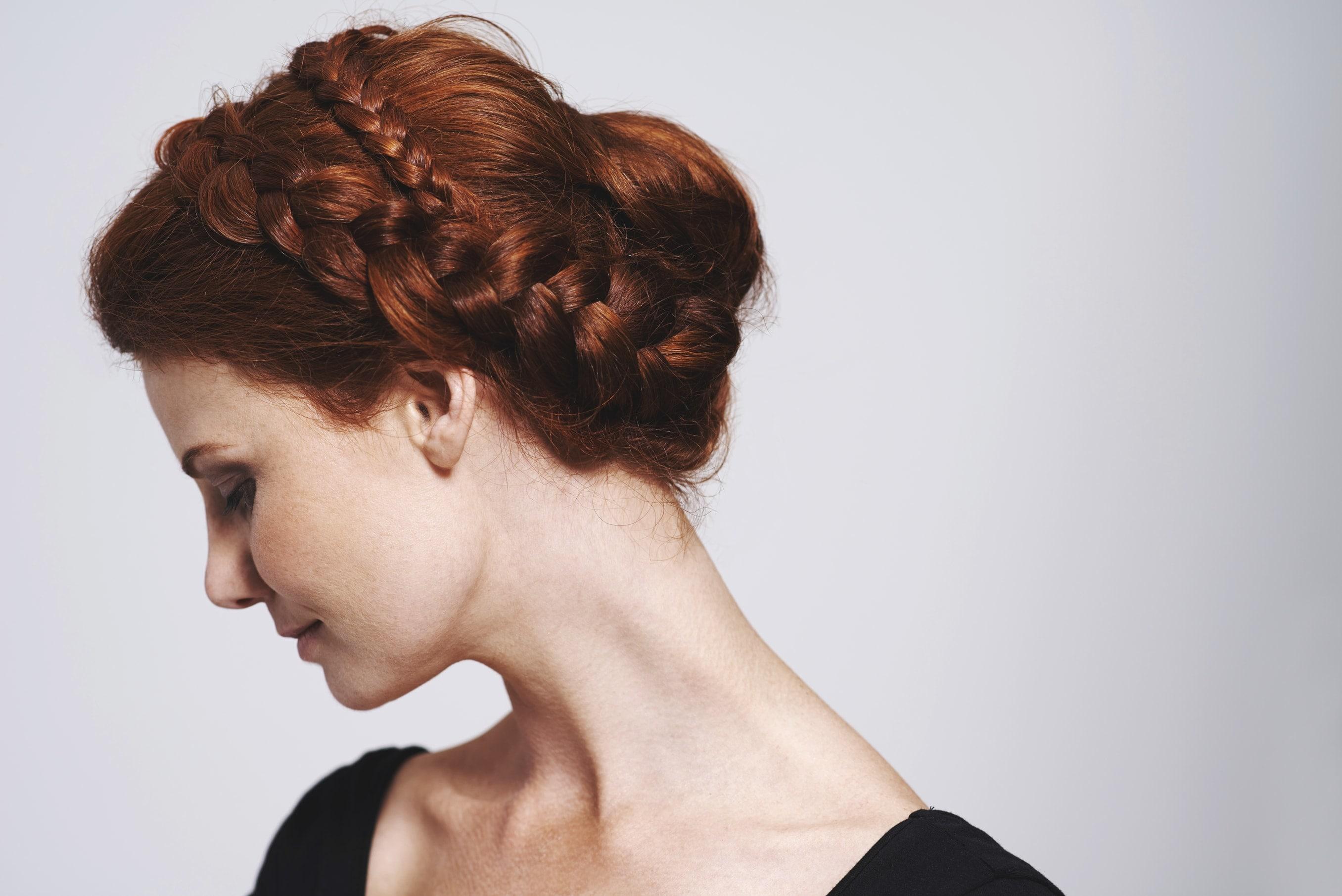 hair bun styles: red head woman with hair styled in a braided headband bun hairstyle