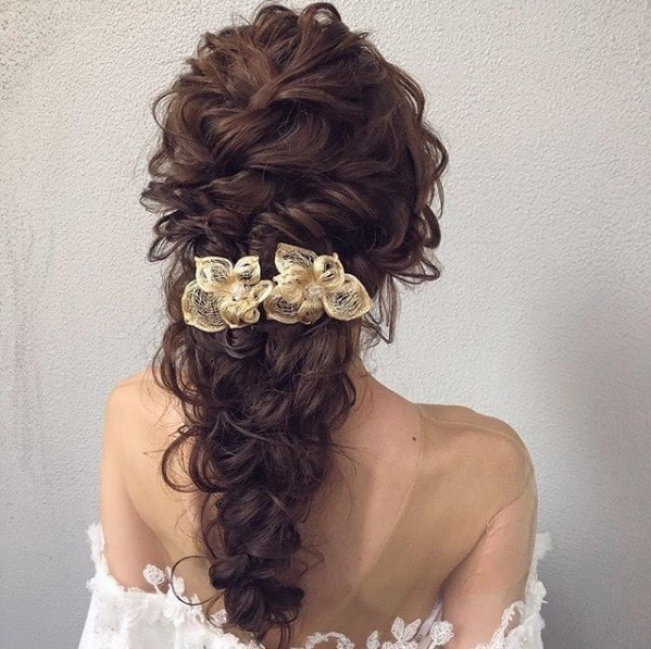 Wedding hairstyles for long hair: Back view of a woman with warm-toned brown curly hair in a twisted braid with floral accessories