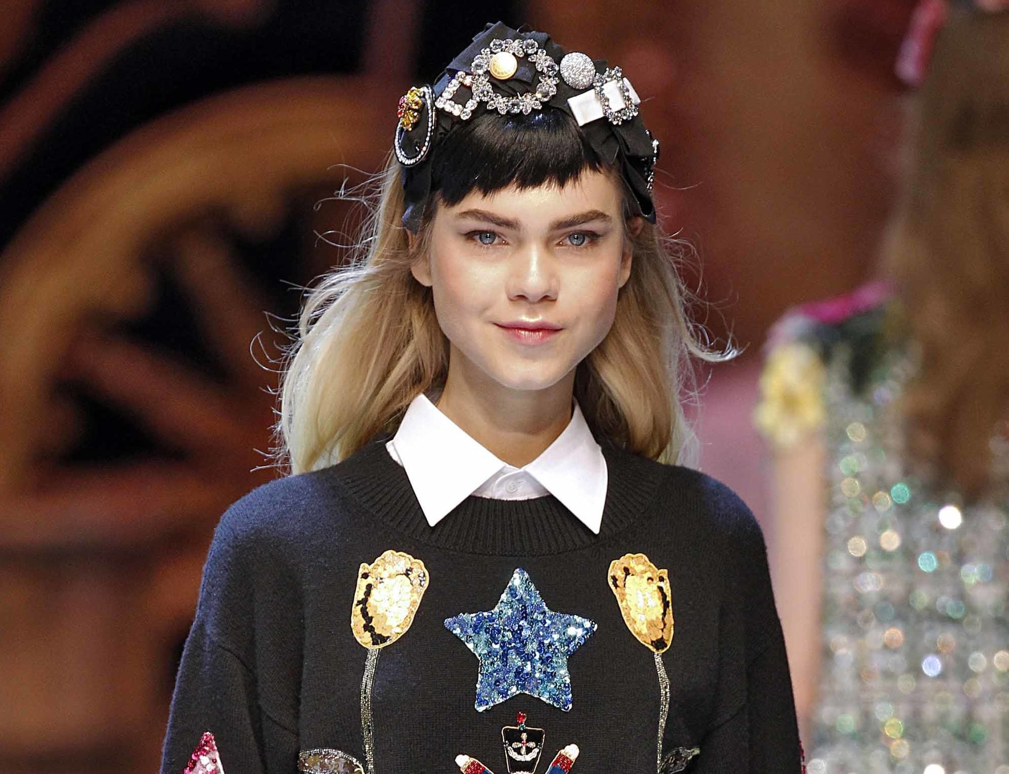 model with long blonde hair with brown micro fringe wearing jewelled headband and logo jumper and white shirt at aw16 fashion week