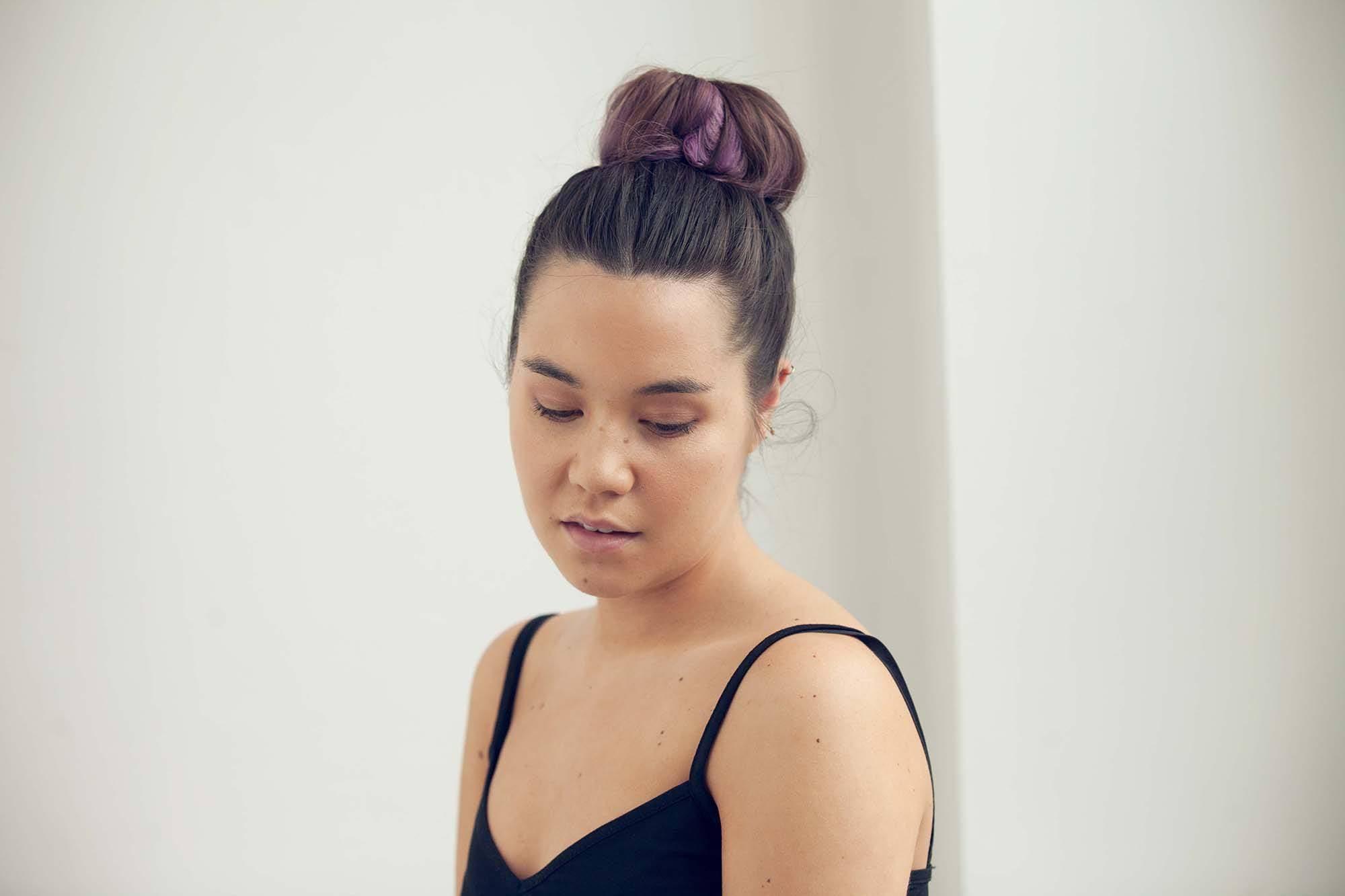 easy bun hairstyles: woman with brown hair styled in a high hair donut bun hairstyle