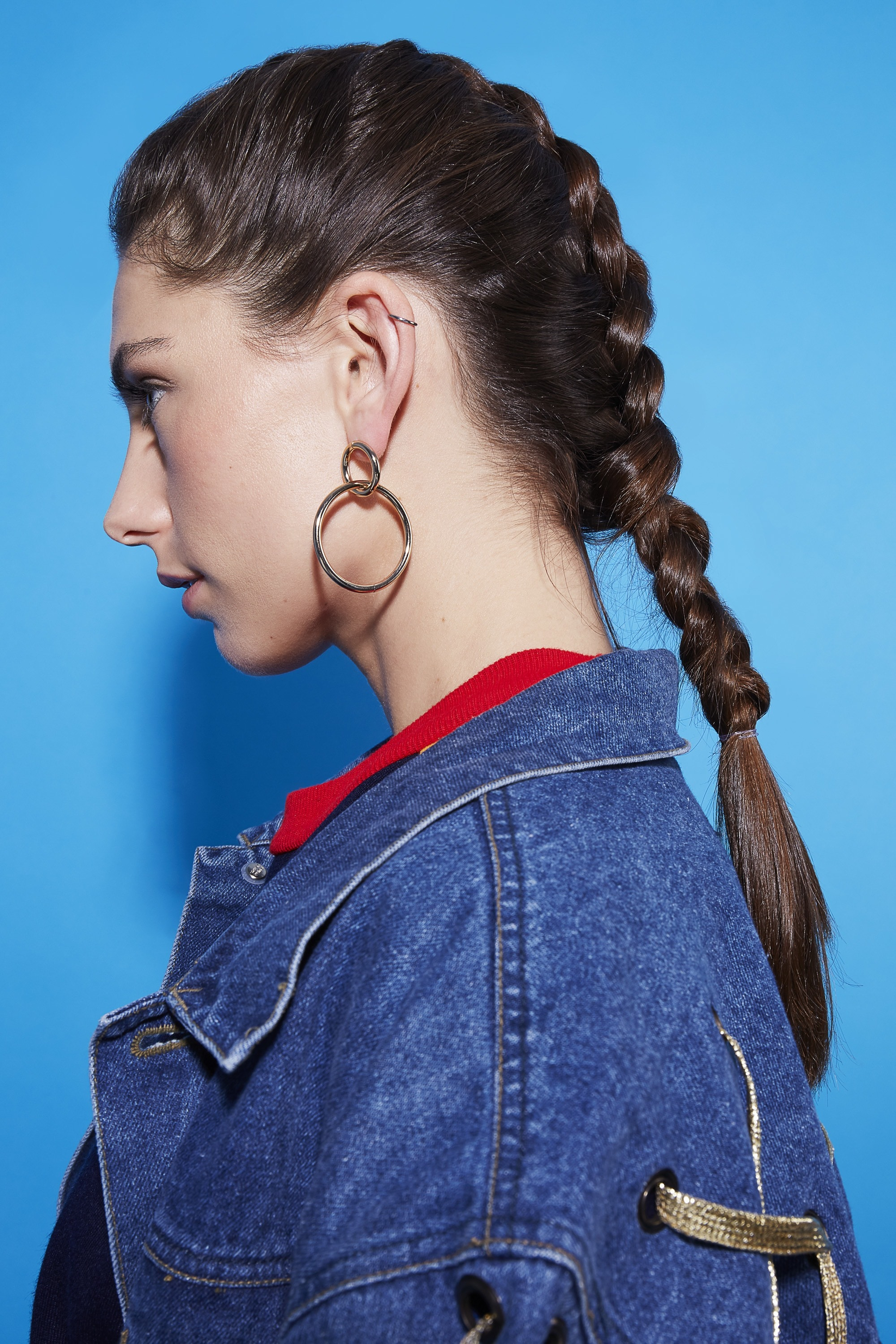 easy sporty hairstyles: close up shot of woman with dutch braid hairstyle, wearing denim jacket and red jumper, with hoop earrings