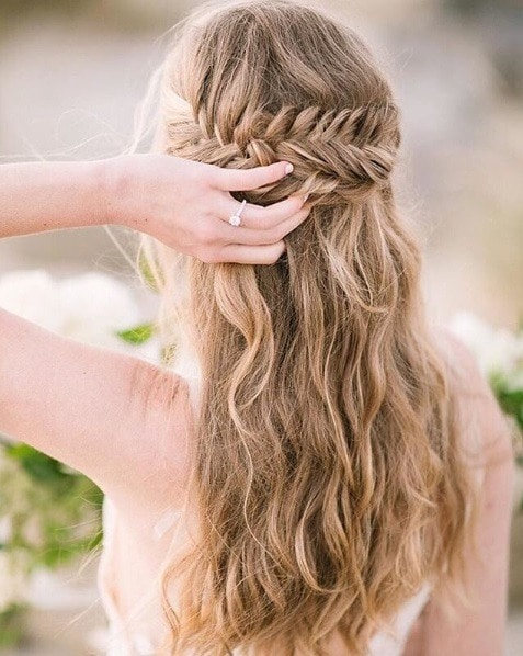 Wedding hairstyles for long hair: Back view of a woman with dirty blonde wavy long hair in a half-up fishtail hairstyle