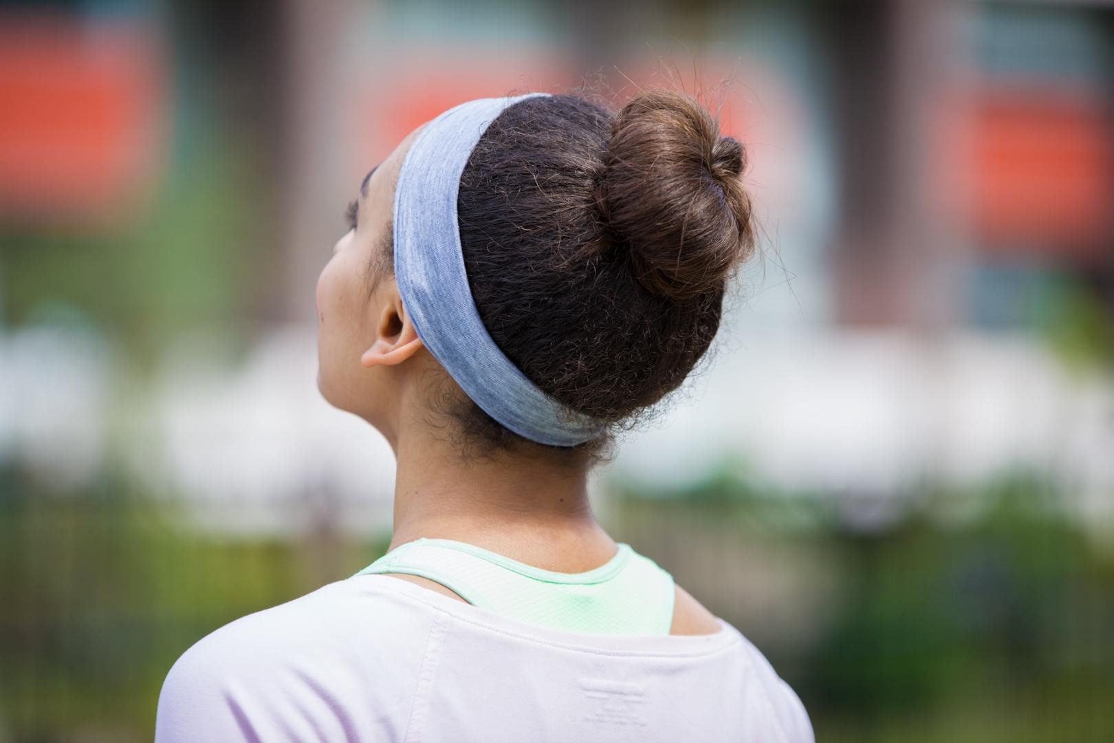 cute sporty hairstyles: close up of woman with natural hair styled into ballerina bun, wearing gym clothing and posing outside