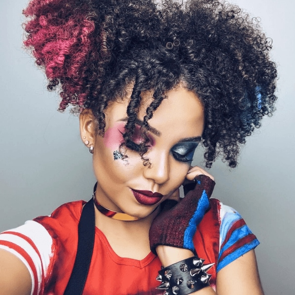 Woman dressed as Harley Quinn with curly natural hair in pigtails with pink and blue chalked ends