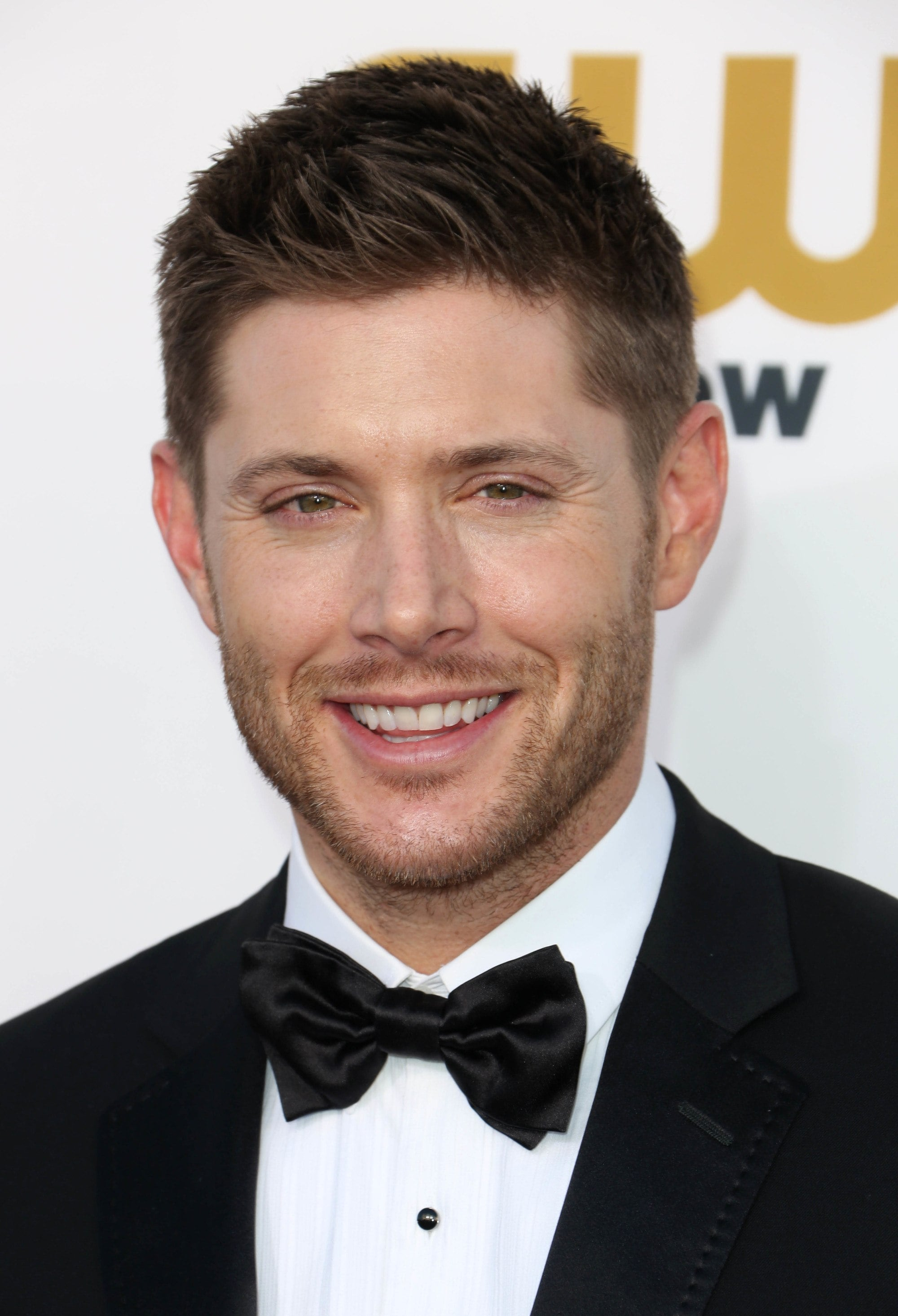 Ivy League haircut: Jensen Ackles with brown hair in a side-swept Ivy League haircut, wearing a tux