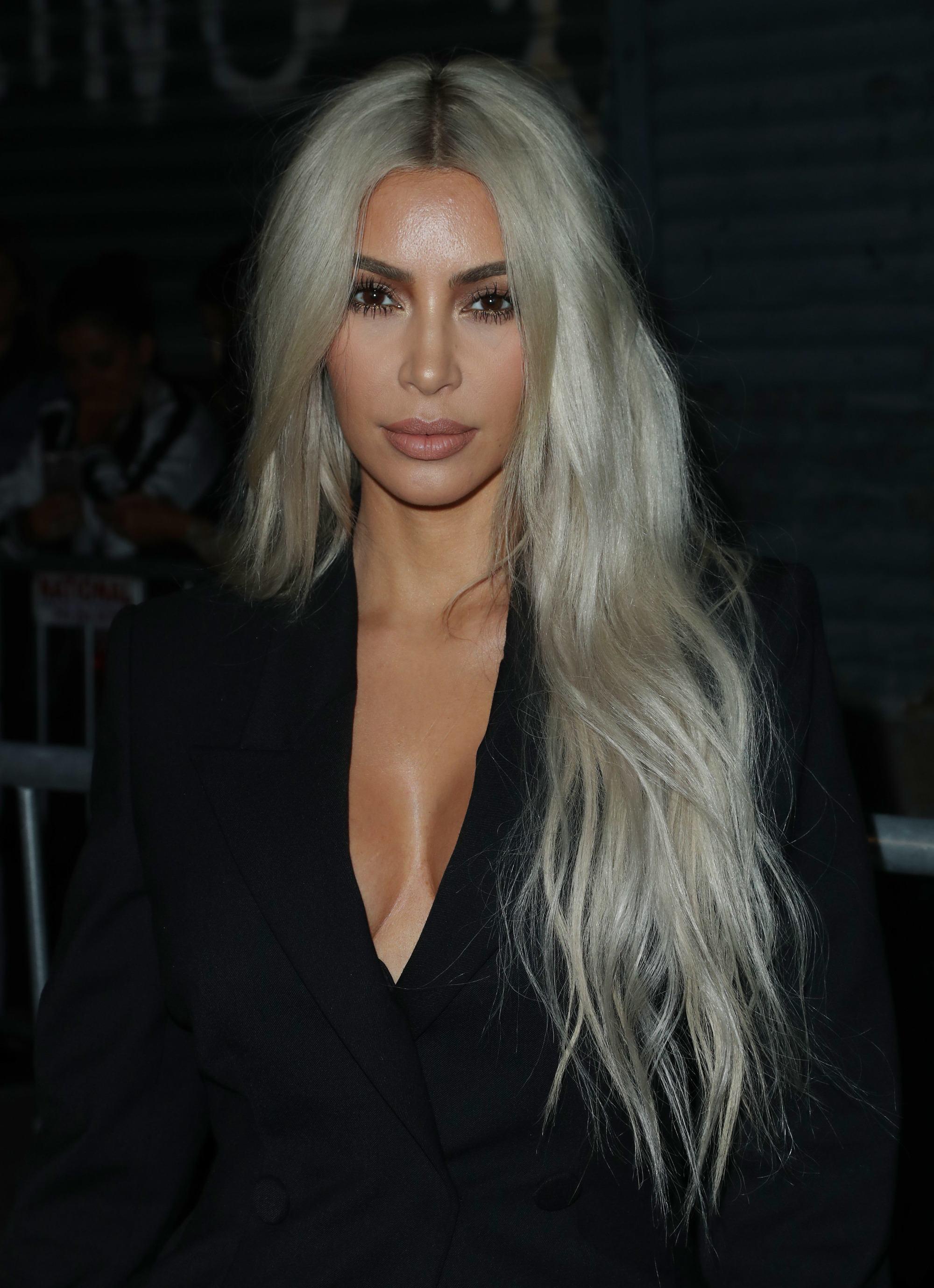 Kim Kardashian rapunzel length silver blonde hair with tousled waves over one shoulder