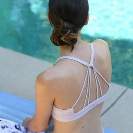back view of a woman sitting by a pool doing yoga with her brunette hair in a low bun