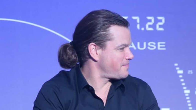 image of matt damon sat down holding a microphone with his long brown hair worn in a low man bun