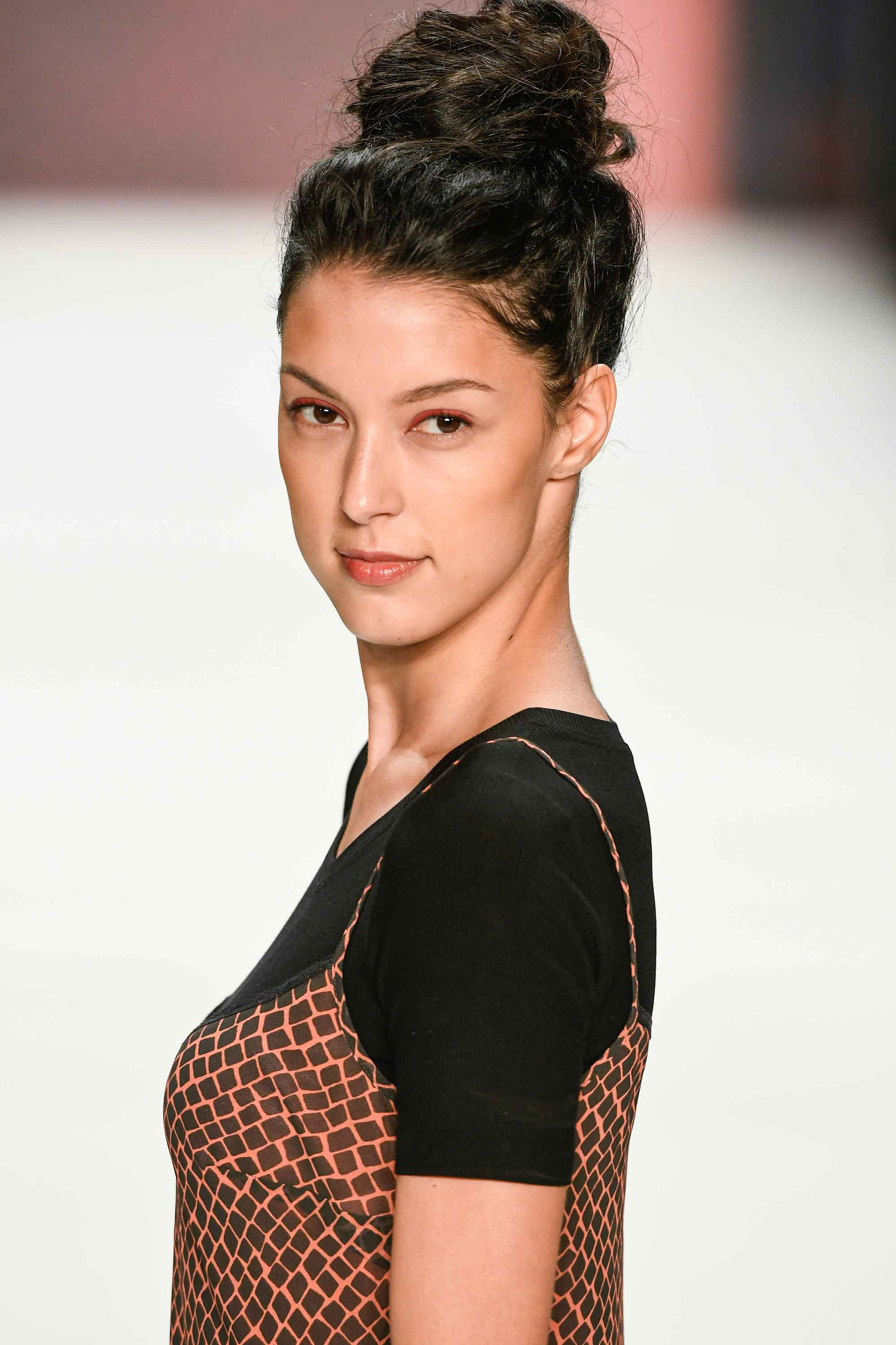 easy bun hairstyles: woman on runway with brown hair styled in a high messy bun hairstyle