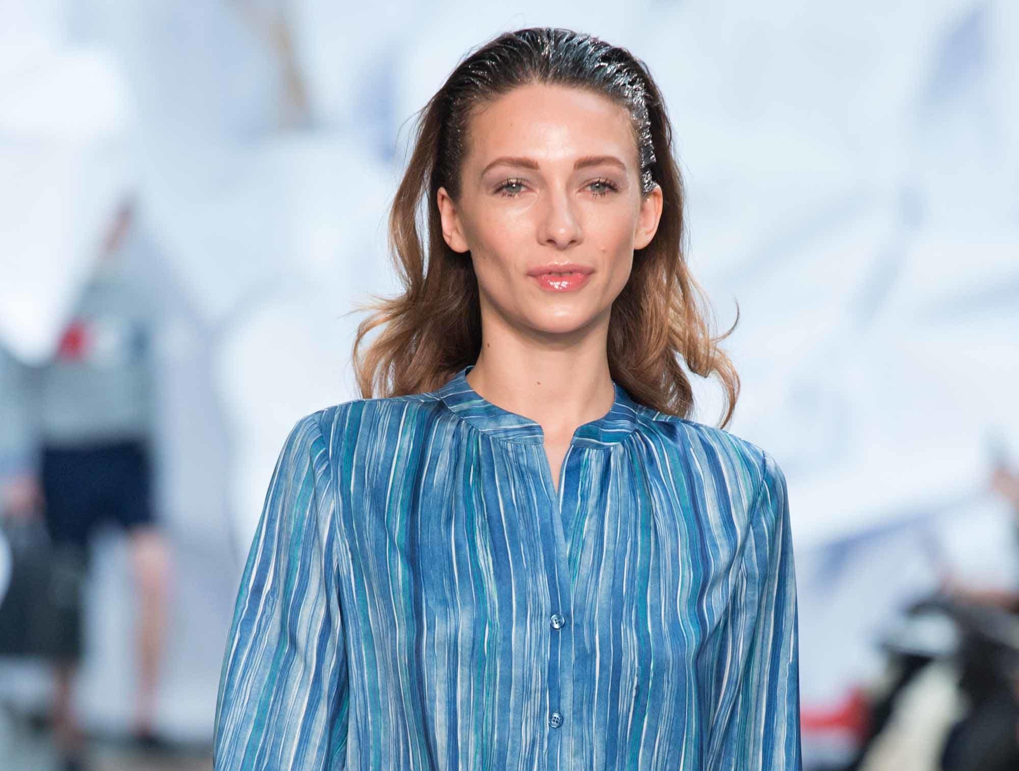 woman with dark blonde wavy hair with pushed back wet look roots wearing stripe blue shirt at aw16 fashion week show