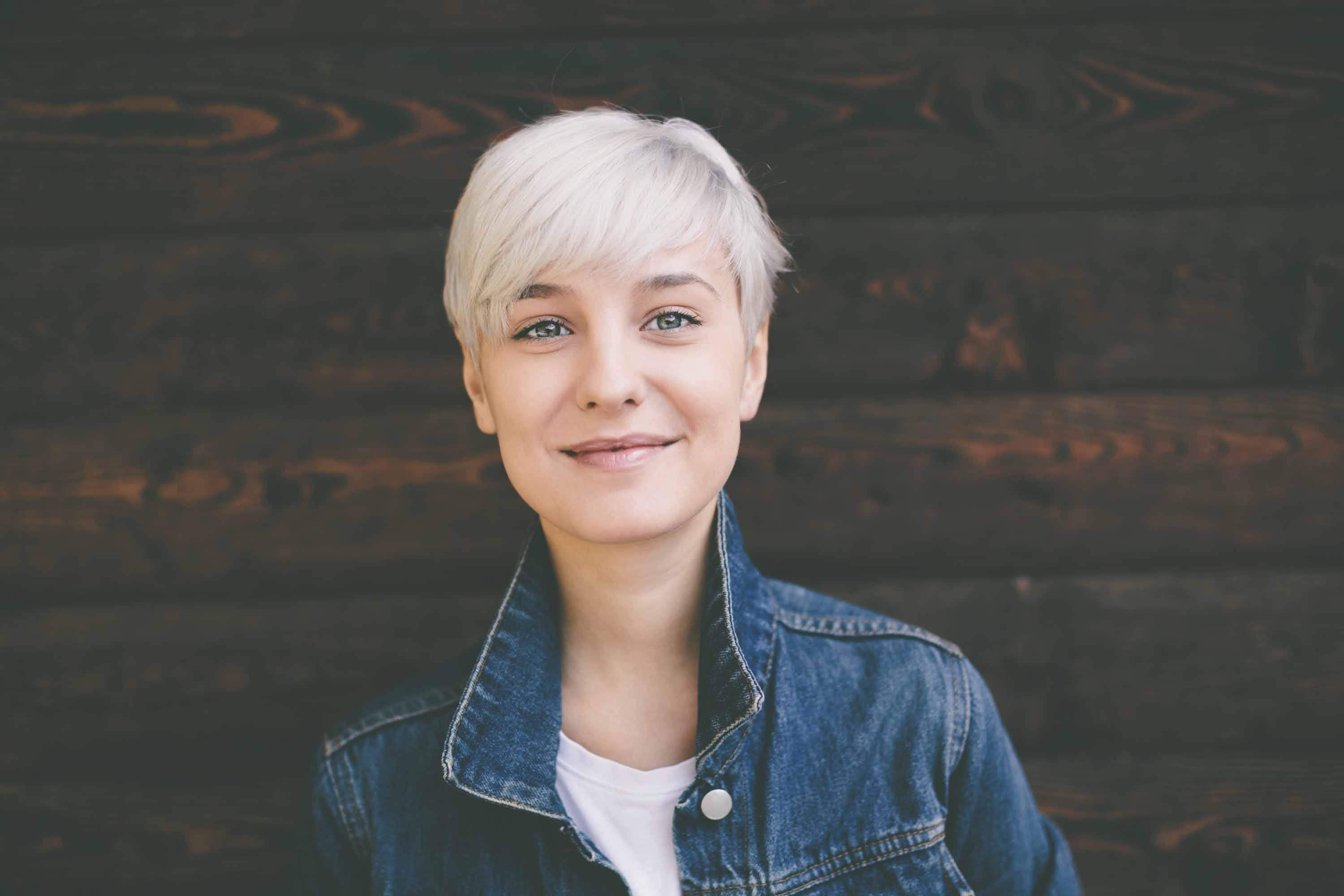 Hairstyles for round faces: blonde woman smiling with pixie haircut