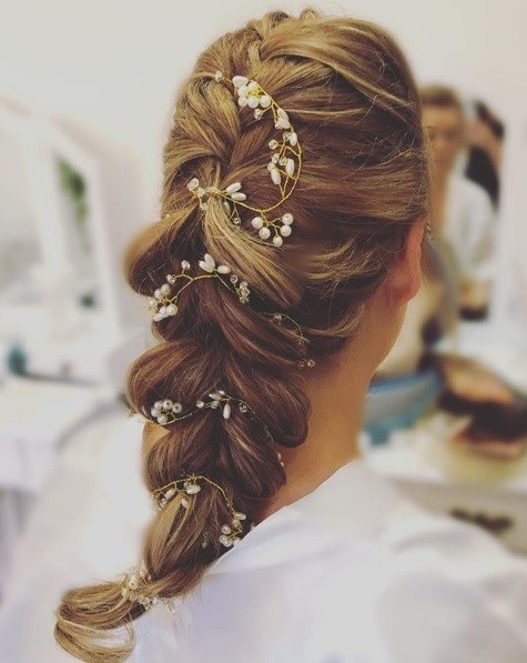 Wedding hairstyles for long hair: Back view of a woman with golden brown hair in a voluminous pull through braid accessorised with small flowers