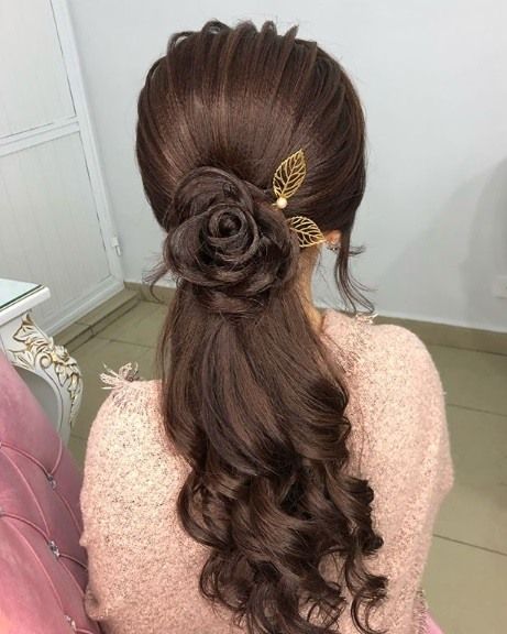 Wedding hairstyles for long hair: Back view of a woman with long curled chestut brown hair with a floral rose braid detail and a gold leaf clip