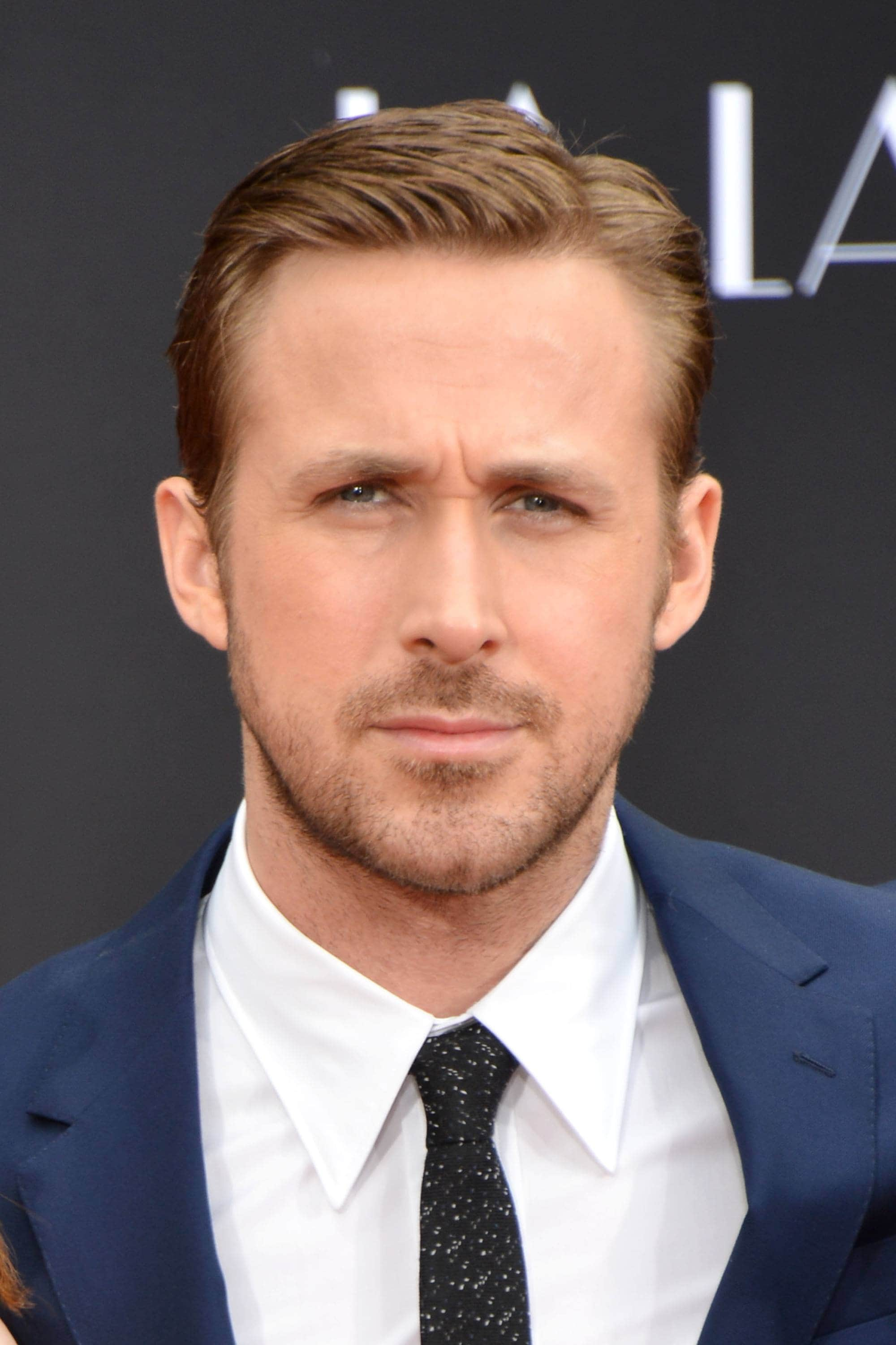 Ivy League haircut: Ryan Gosling with light brown hair worn in an Ivy League haircut, wearing a blue blazer, white shirt and tie