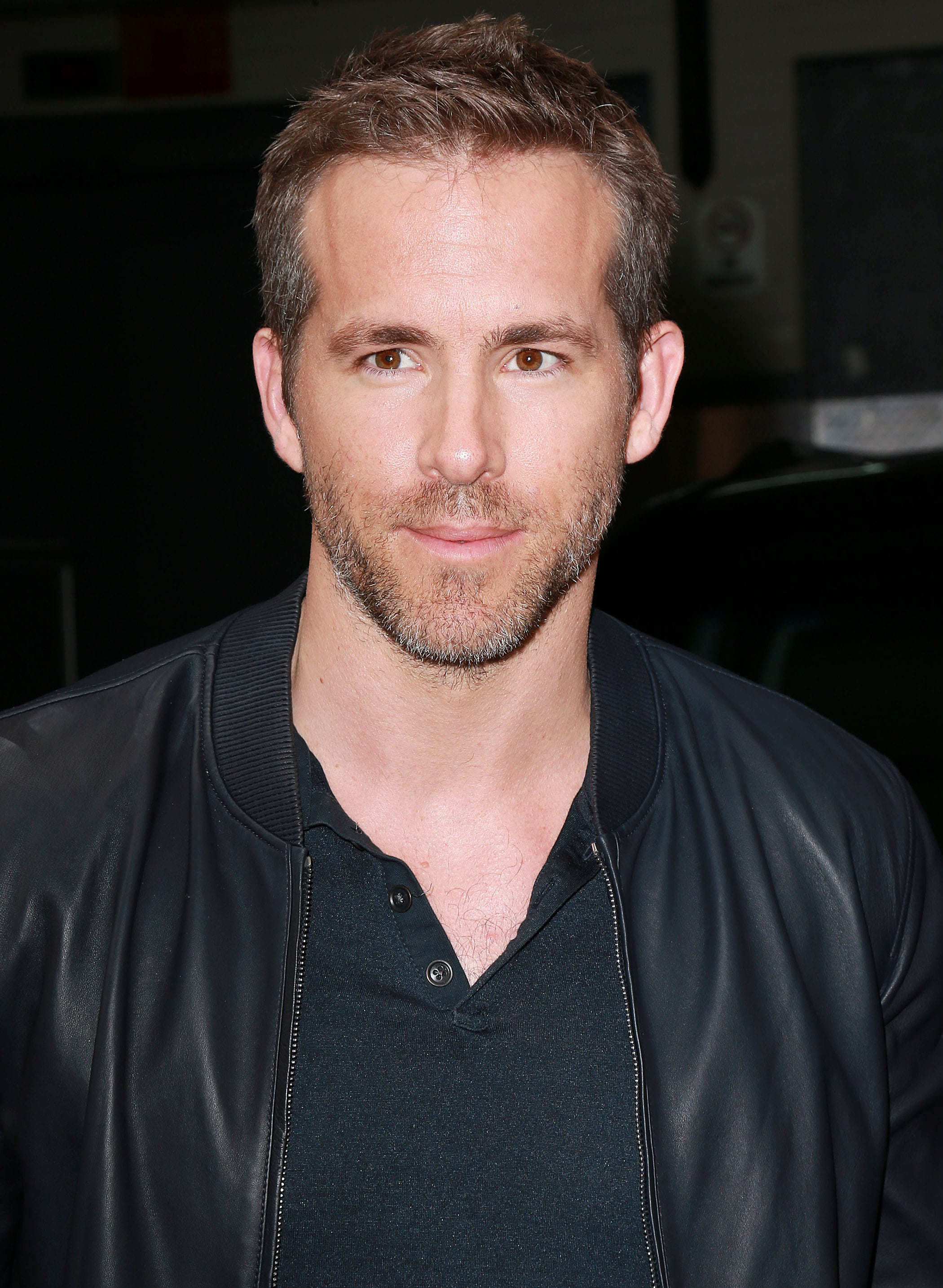Ivy League haircut: Ryan Reynolds with brown hair in an Ivy League Haircut, wearing a black top and jacket