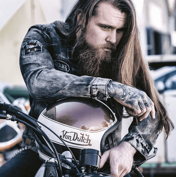 front view image of a man on a motorbike with long hair and a full beard