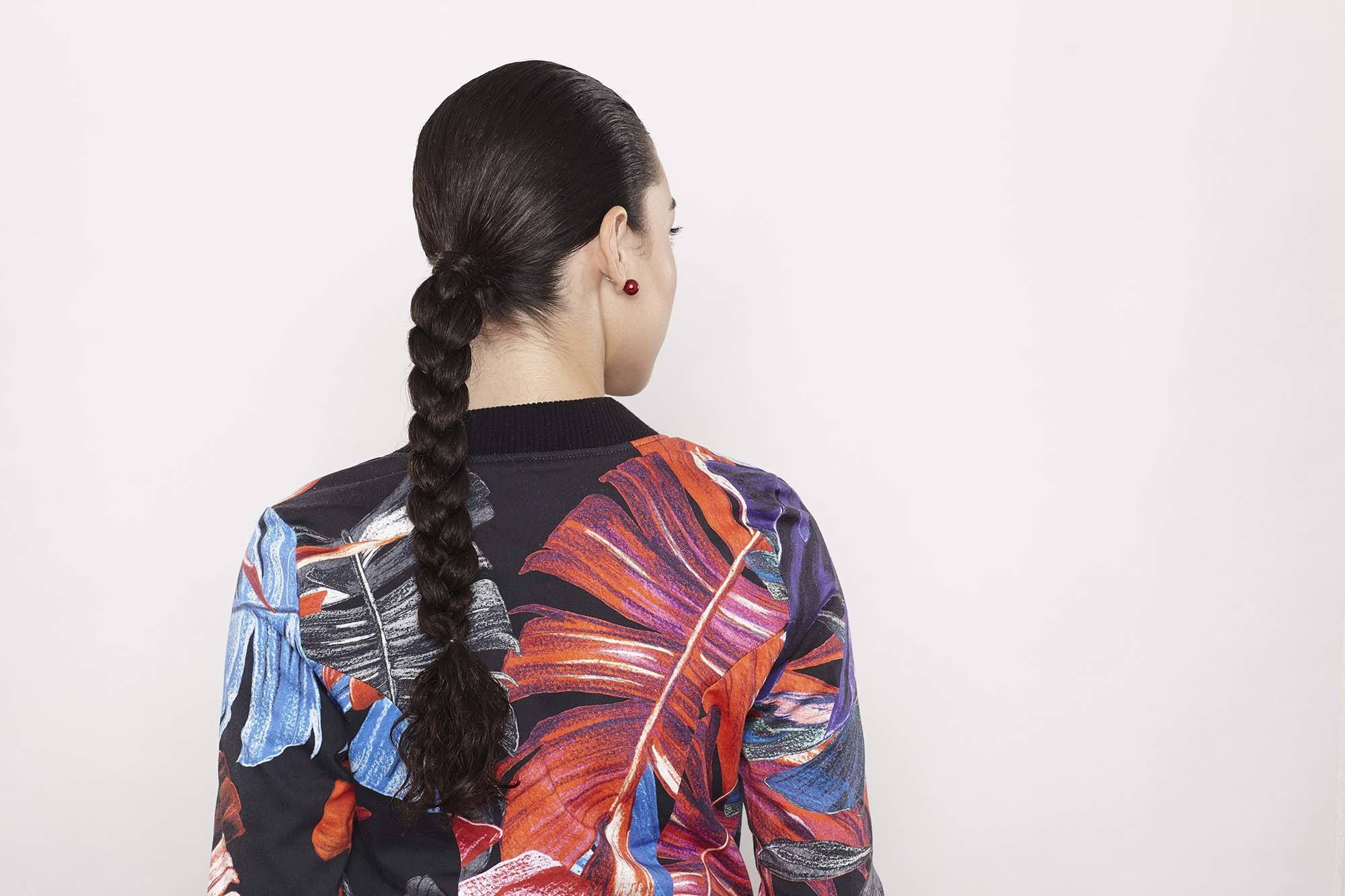close up shot of woman with sporty braided hairstyle, wearing floral gym clothing and posing
