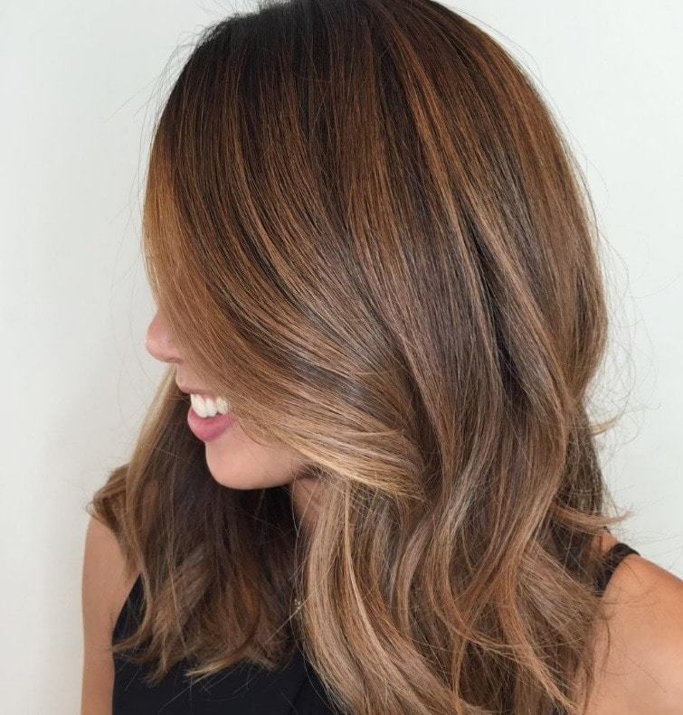 side shot of a woman with long brunette hair with light brown highlights