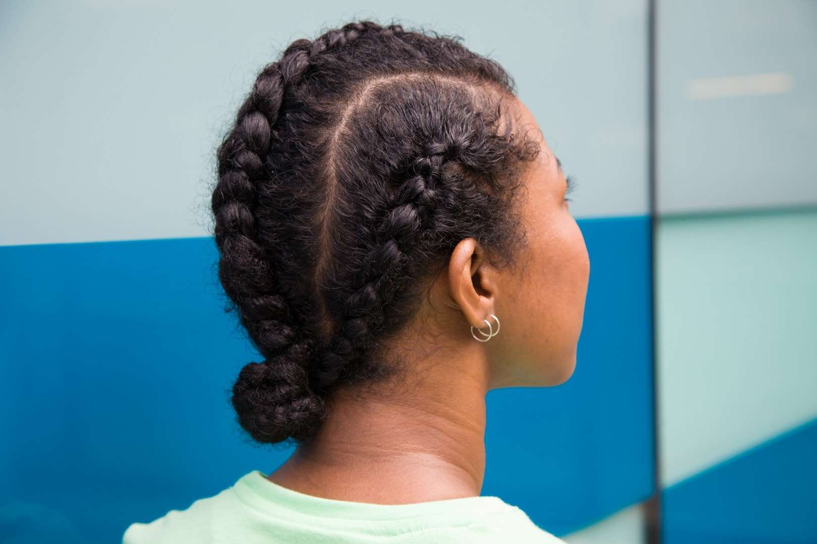close up shot of woman with three part cornrow hairstyle, wearing green sporty top and posing outside