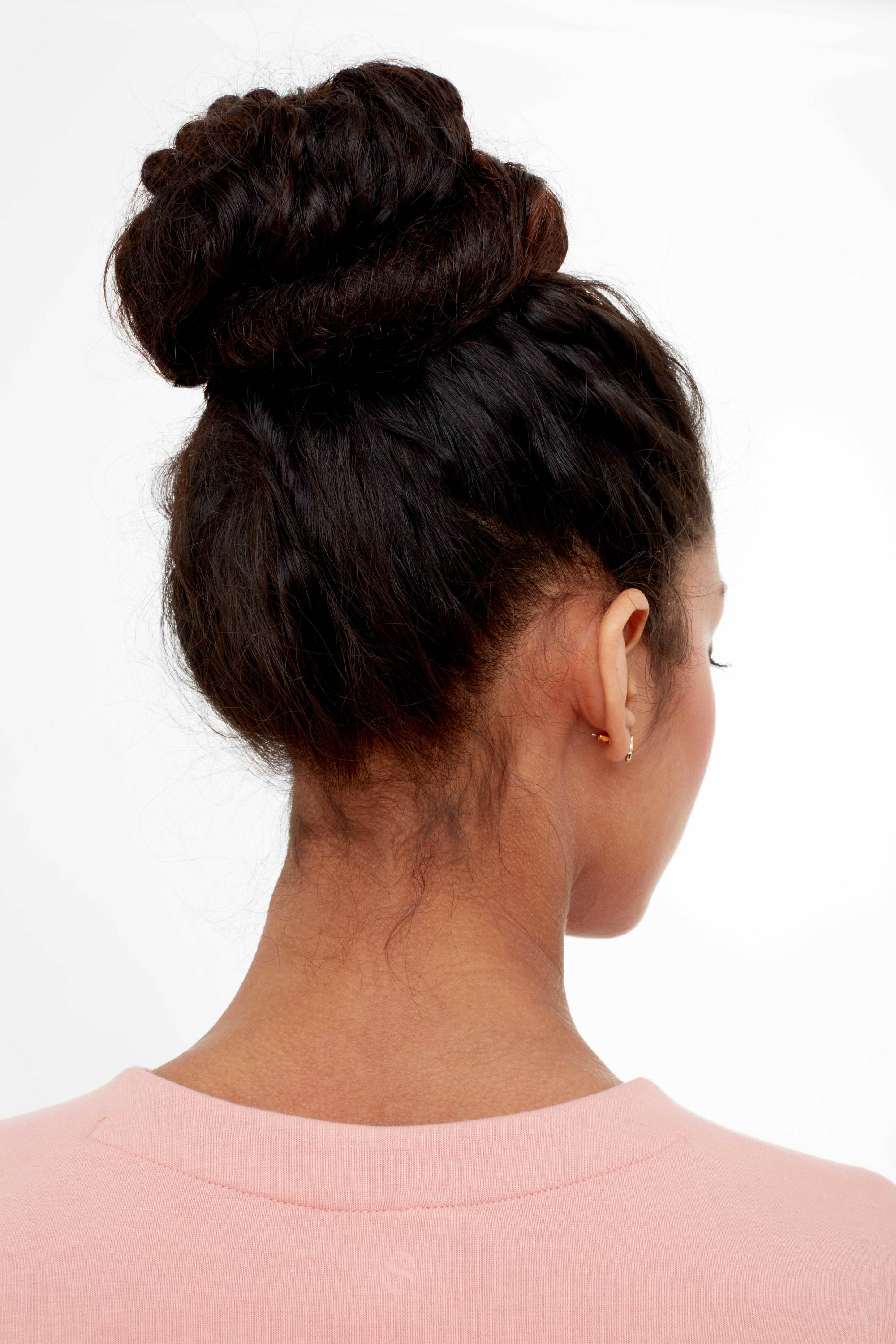 Hairstyles for thick hair: Back shot of model with dark brown long thick hair styled into a twisted bun, wearing pink jumper in studio setting