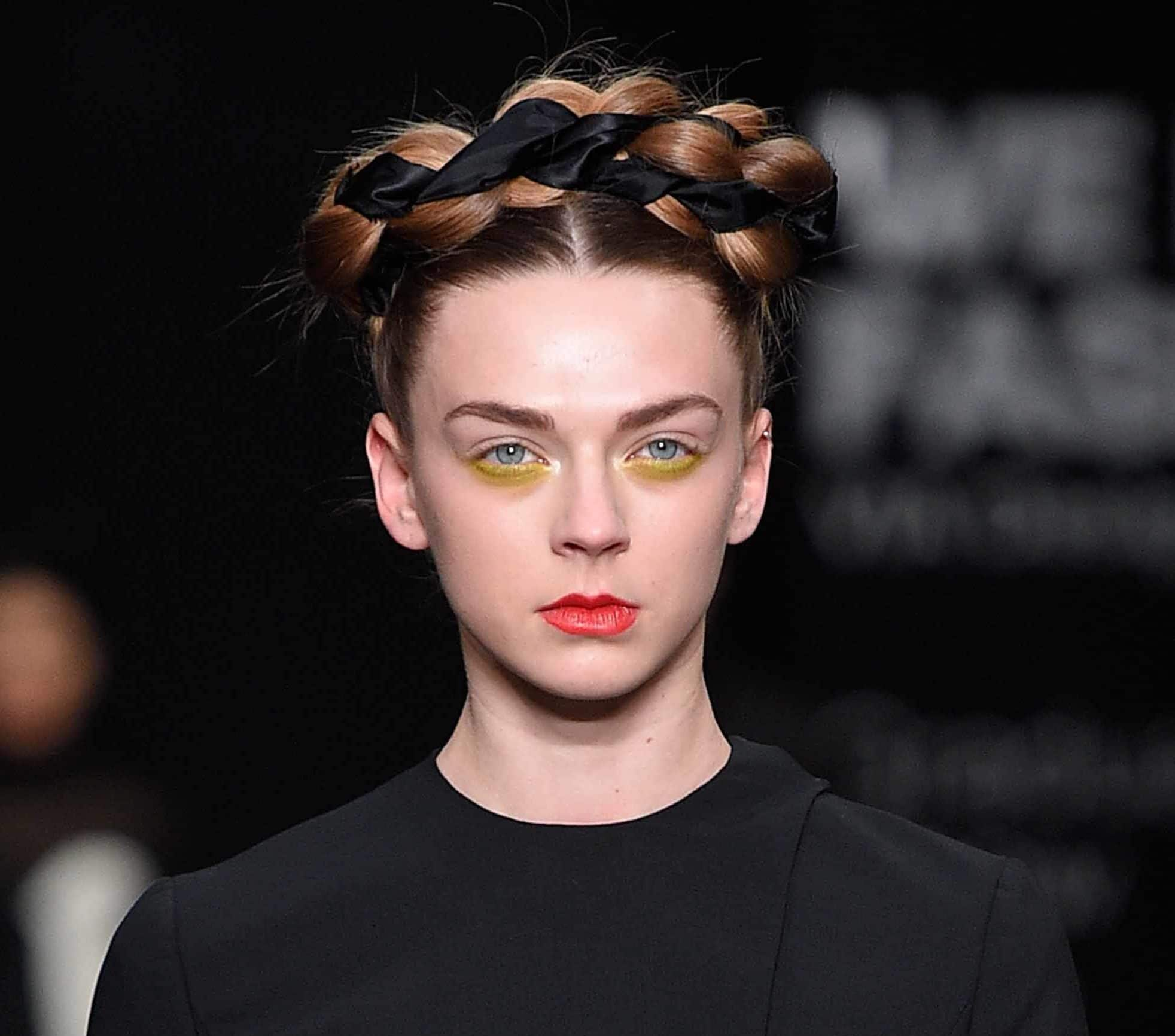 model with brown auburn hair with crown braid woven with ribbon wearing yellow eye makeup, red lips and black dress at aw16 fashion week