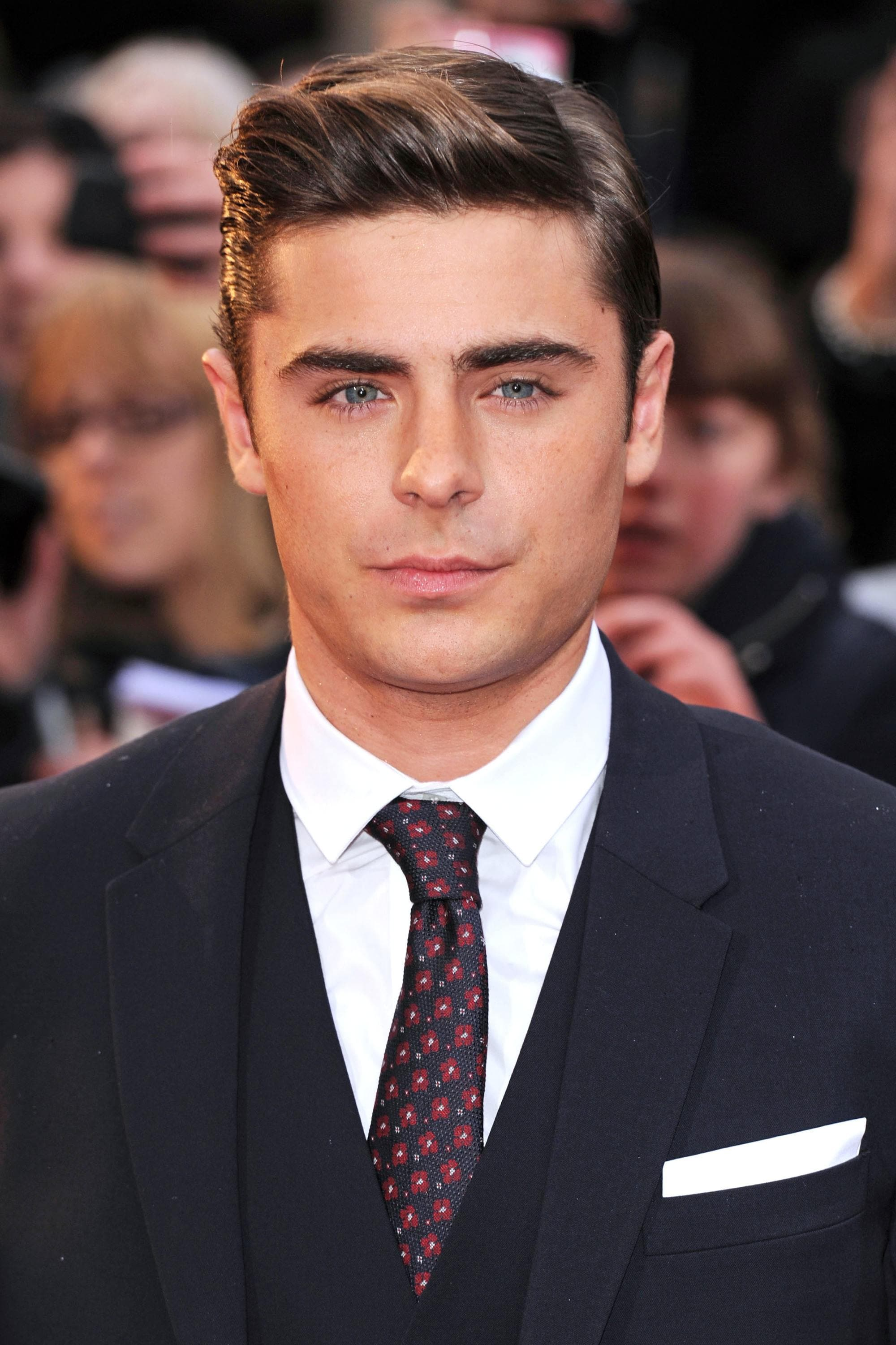 Ivy League haircut: Zac Efron with brown hair in a long Ivy League haircut, on the red carpet wearing a suit and tie
