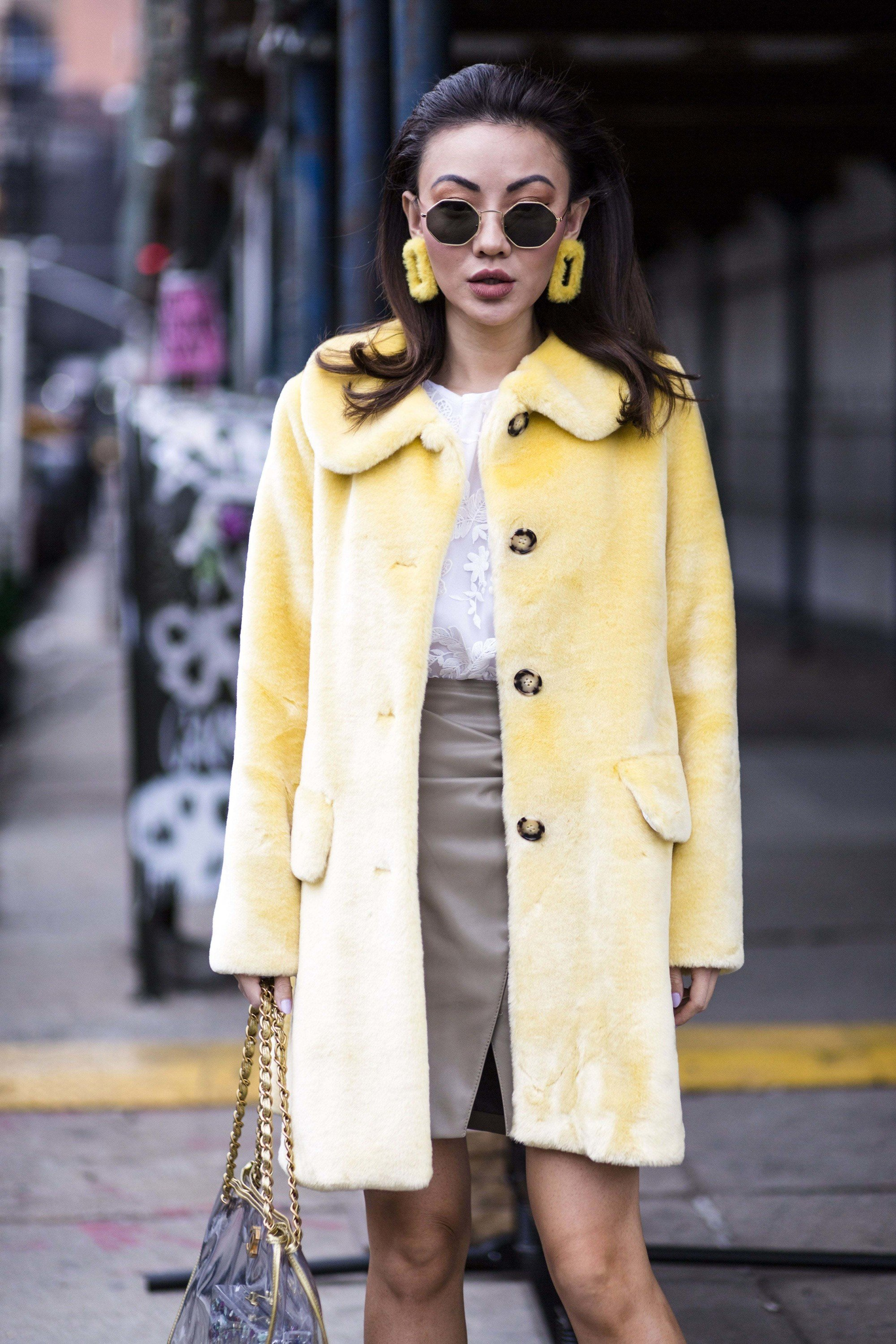 nyfw street style shot of an asian woman in a 60s outfit with pushed back hair