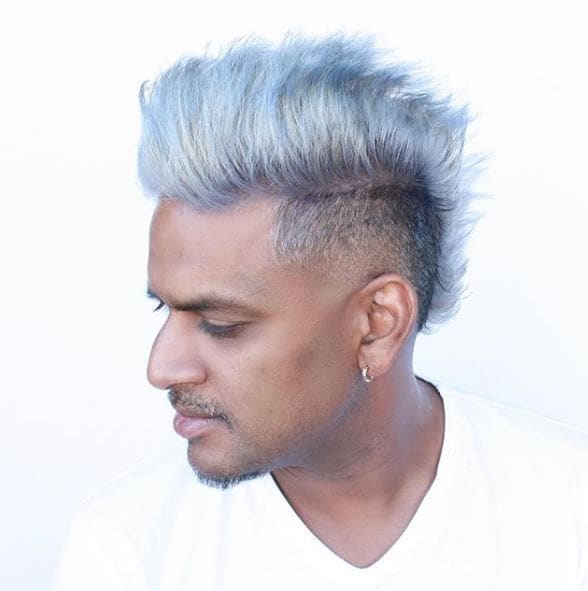 Asian man with silver mohawk hairstyle looking down