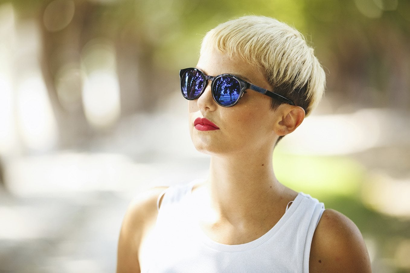 How short should I cut my hair? Woman with summery-looking bleached blonde bowl cut and dark undercut
