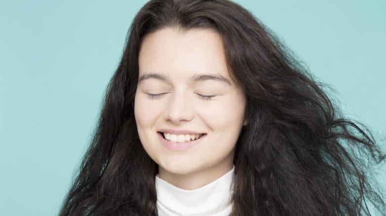 model with dark brown curly long hair using hair dryer